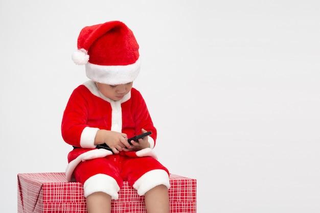 Bebé asiático con traje de santa claus sosteniendo teléfono móvil y sentado en caja de regalo aislada en la pared blanca