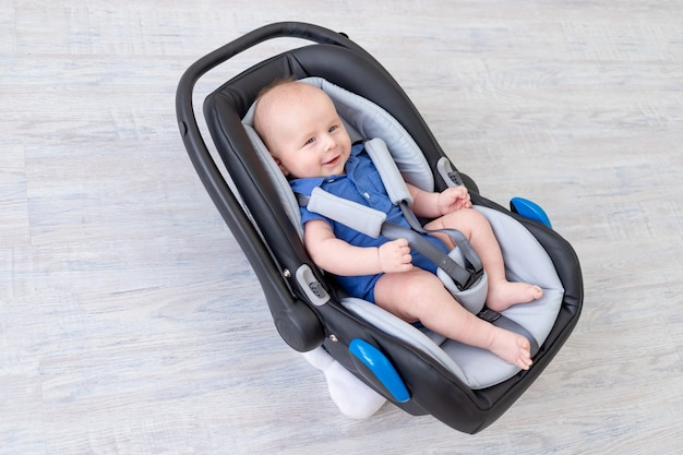 Bebé en el asiento del coche, recién nacido feliz acostado abrochado en el cinturón de seguridad
