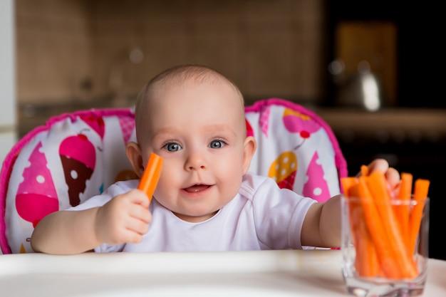 Bebé en un asiento de niño comiendo verduras