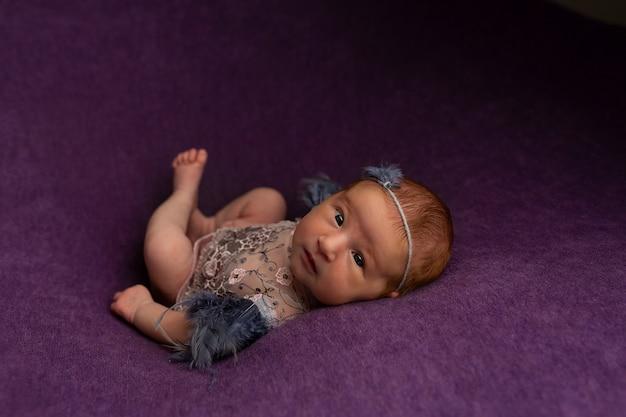 Bebé bastante recién nacido en vestido rosado en fondo de la materia textil. con una diadema. accesorios e ideas fotográficas para recién nacidos para la primera sesión de fotos