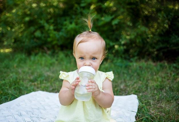 Bebé bebe agua de una botella en la naturaleza.