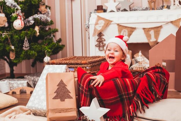 Bebé bonito feliz vestido con traje de santa claus con regalos de navidad