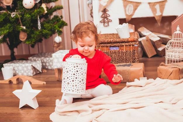 Bebé bonito feliz vestido con vestido rojo con regalos de navidad
