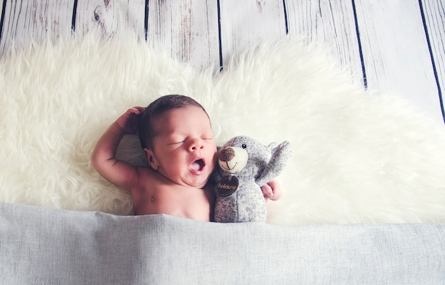 Bebé bostezando junto a un animal de peluche