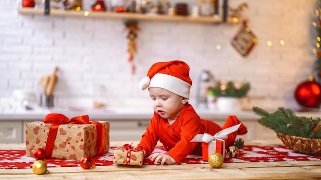 Bebé con cajas de regalo sobre la mesa con adornos navideños