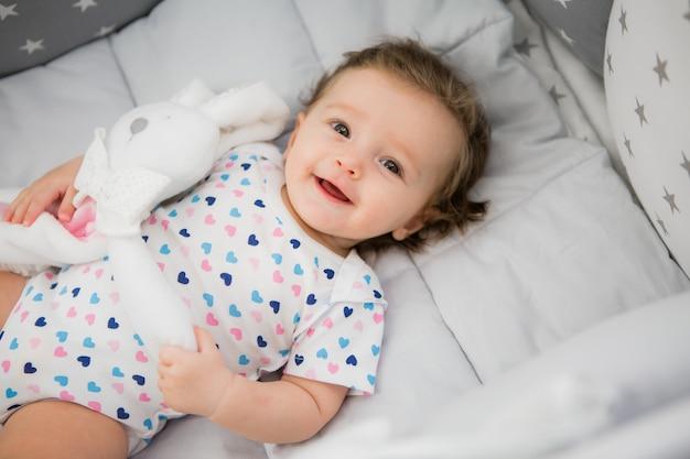 Bebé en una cama de bebé sobre un fondo claro