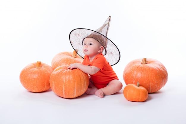 Bebé en camiseta naranja sobre un fondo blanco.