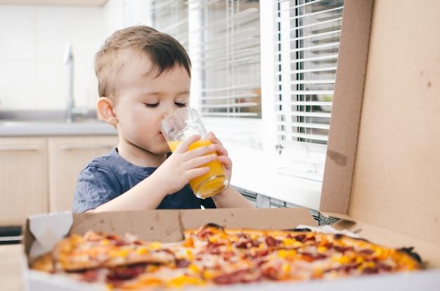 Bebé en la cocina bebiendo jugo de naranja y comiendo una pizza grande