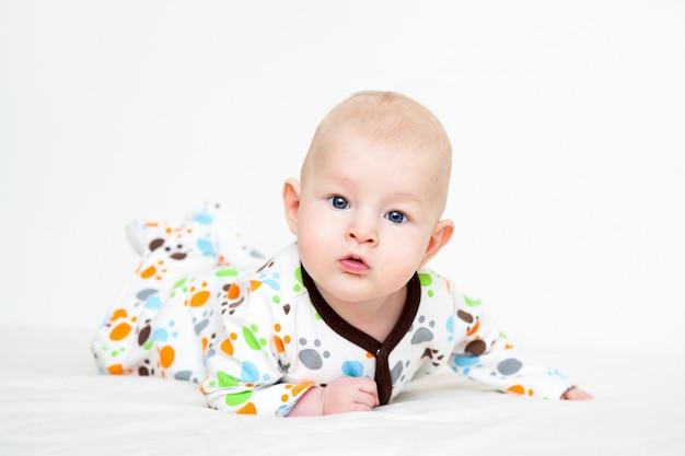 Bebé en color deslizarse sobre la cama acostado sobre su estómago
