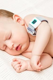 Bebé en la cuna mide la temperatura corporal.