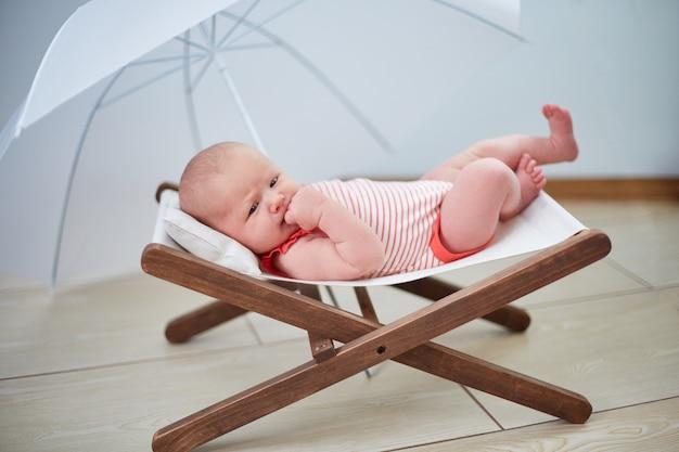 El bebé está descansando en una tumbona bajo una sombrilla en casa.