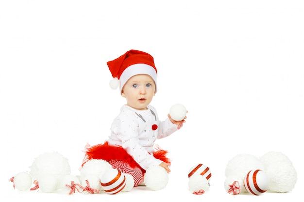 Bebé divertido hermoso en un sombrero de la navidad aislado