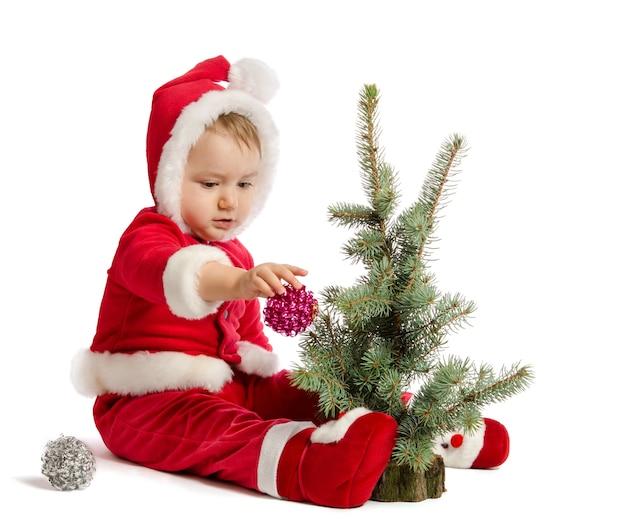 Bebé divertido en ropa de santa claus está decorando el árbol de navidad sobre fondo blanco.
