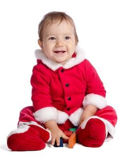 Bebé divertido en ropa de santa claus sobre fondo blanco con cubos