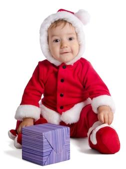 Bebé divertido en ropa de santa claus sobre fondo blanco con regalo