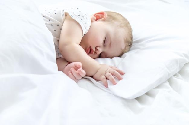 Bebé duerme en una cama blanca