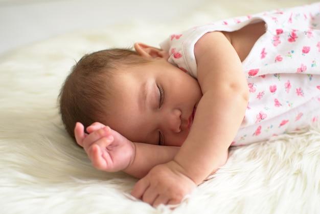 Bebé está durmiendo bien en la alfombra blanca