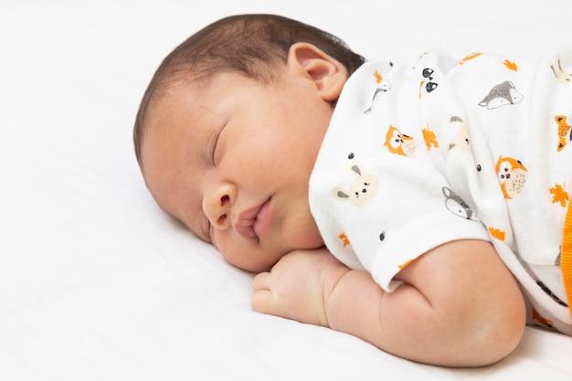Bebé durmiendo en la cama con los brazos debajo de la cabeza.