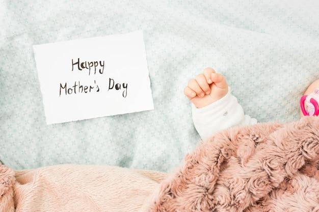 Bebé durmiendo en la cama junto a la inscripción happy mothers day