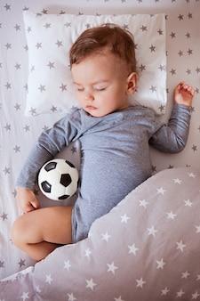 El bebé está durmiendo en una cuna con una pelota de fútbol en la mano.
