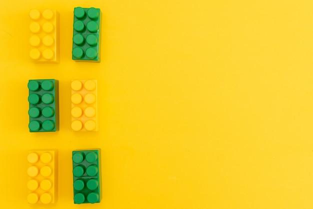 El bebé embroma el marco de los juguetes con el oso de peluche, coche de madera del juguete, ladrillos coloridos en fondo amarillo.
