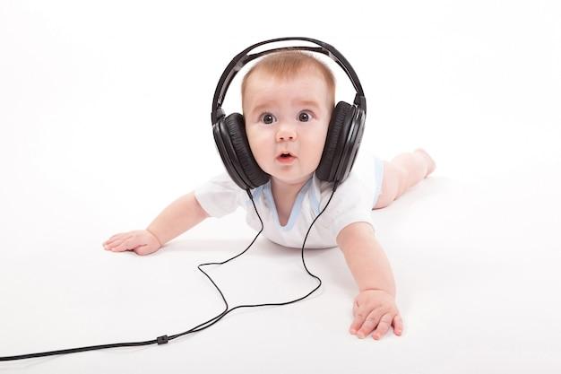 Bebé encantador con auriculares escuchando
