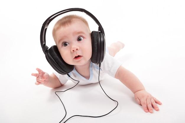 Bebé encantador en un blanco con auriculares escuchando