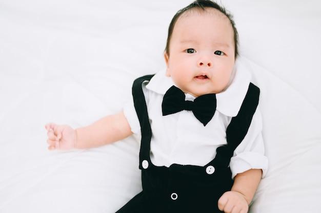 Bebé feliz de 2 meses. niño pequeño en una camisa blanca y corbata de lazo. retrato de niños hombre elegante en moda un esmoquin de pajarita.