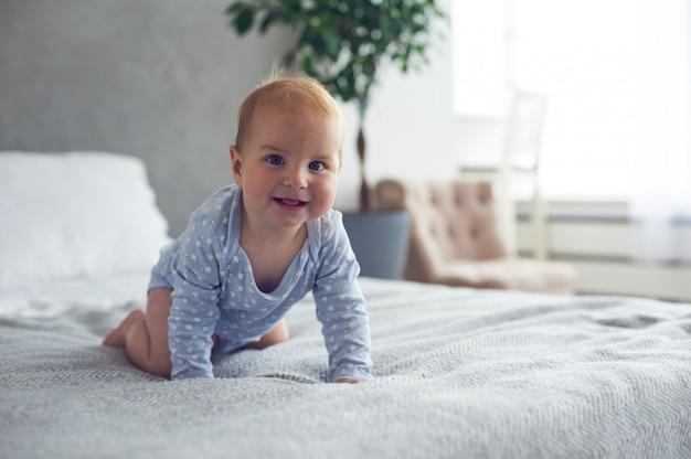 Bebé feliz de 8 meses gateando en la cama en casa