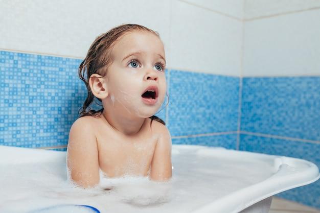 El bebé feliz alegre del niño de la diversión que toma un baño que juega con espuma burbujea.