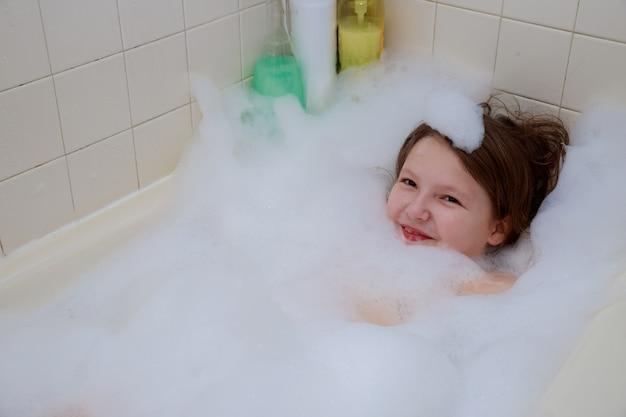 Bebé feliz en el baño, nadando en la ducha de espuma.