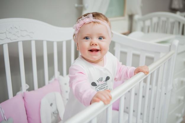 Bebé feliz en una cama en casa