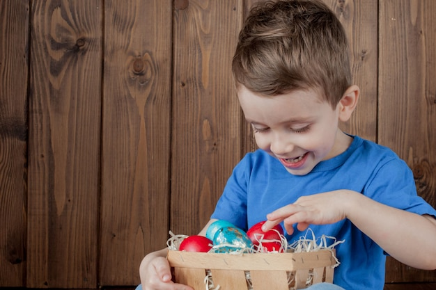 Bebé feliz con una canasta de huevos de pascua sobre fondo de madera