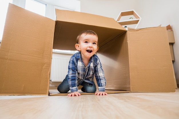 Bebé feliz que se arrastra dentro de una caja de cartón abierta en casa