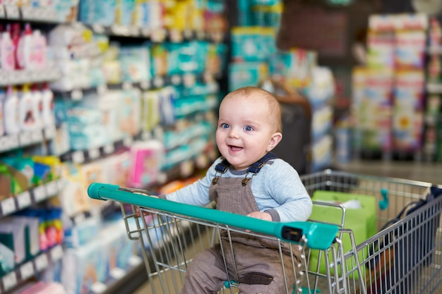 Bebé feliz que sonríe en carretilla en tienda de comestibles