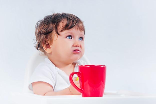 Bebé feliz sentado y comiendo
