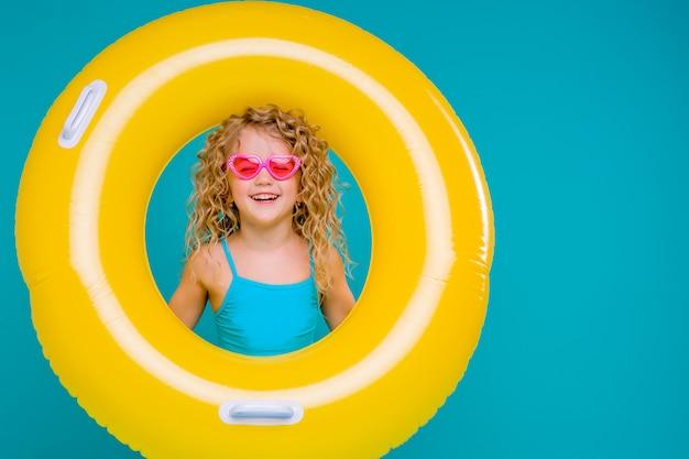 Bebé feliz en traje de baño con el círculo aislado en fondo azul