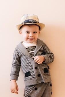 Bebé feliz en traje gris, sombrero en pared de luz
