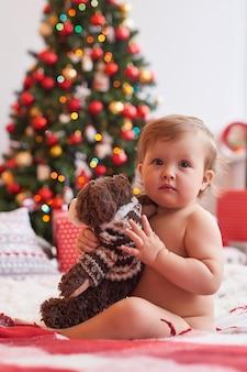 Bebé en el fondo del árbol de navidad con un juguete
