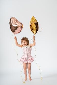 Bebé con globos y estrellas en forma de corazón