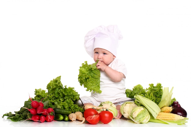 Bebé con gorro de chef rodeado de verduras