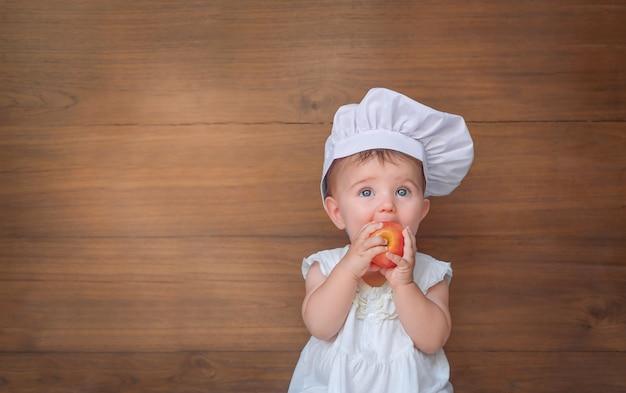Bebé con gorro de cocinero. el niño muerde la manzana