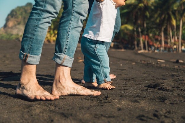 Bebé haciendo los primeros pasos con los padres en la playa de arena
