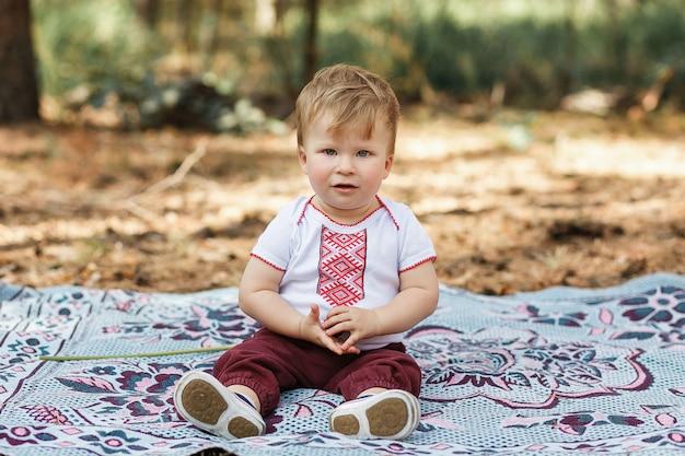Bebé hermoso un año que se sienta en la tierra. el niño se divierte en el bosque de primavera