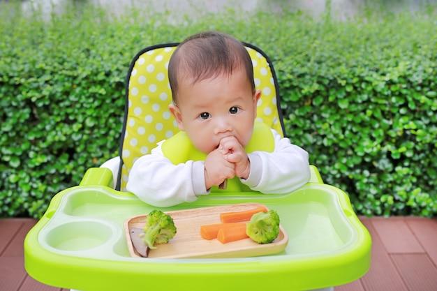 Bebé infantil asiático comiendo por baby led weaning (blw). concepto de alimentos de dedo.