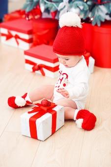 Bebé infantil divertido desempaqueta caja de regalo de navidad. feliz navidad y próspero año nuevo.