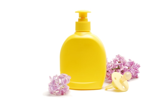 Bebé jabón líquido, chupete y flores lilas aisladas sobre fondo blanco.