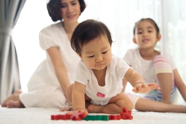Bebé joven asiático que juega los juguetes de madera con la ayuda de su hermana y madre en casa.