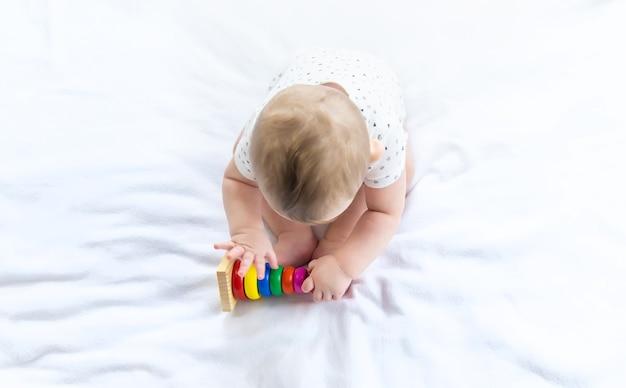 Bebé juega con una pirámide de juguete en casa.