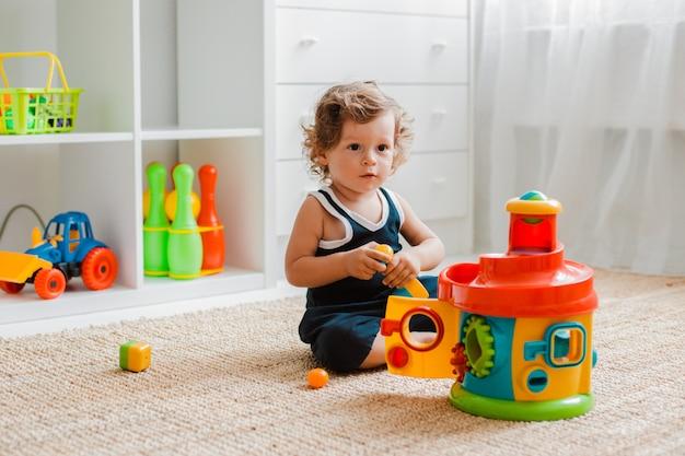 El bebé juega en el piso de la habitación con juguetes educativos de plástico.